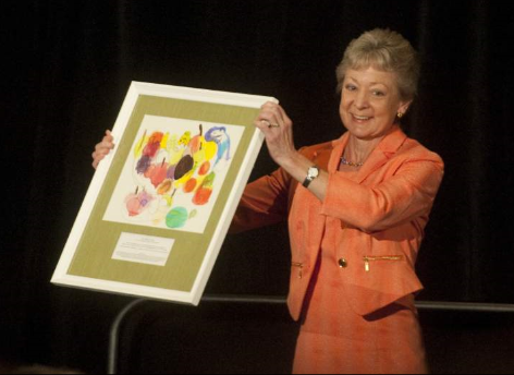 Kim Tillotson Fleming with a painting done by a United Way recipient of service. Source: Pittsburgh Tribune-Review